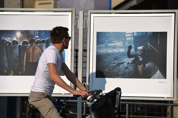 A passer-by at the exhibition of the missing photojournalist Rossiya Segodnya photographer Andrei Stenin's works in front of the news agency building in Moscow. - Sputnik International