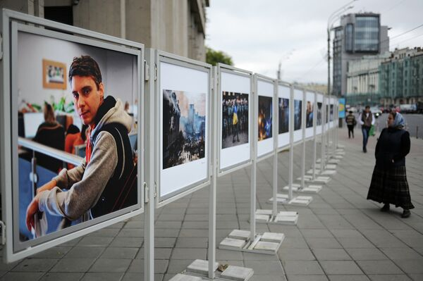 A resident of Moscow looking at the works of the Rossiya Segodnya photojournalist Andrei Stenin, killed in Ukraine, near the agency building in Moscow. - Sputnik International