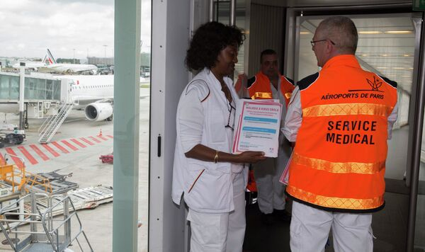 Paris airport doctors pose with copies of the leaflet which will be given to passengers arriving from Ebola infected zones, as they stand at the plane's arrivals bridge during a press visit at the Charles de Gaulle International Airport in Roissy, near Paris October 17, 2014. - Sputnik International